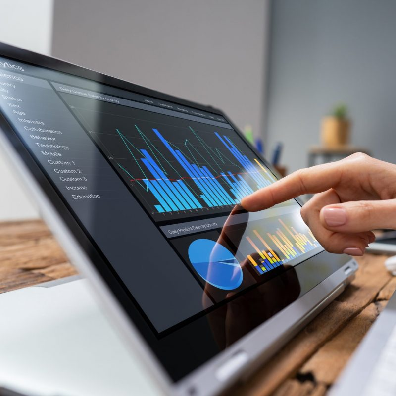 Close-up Of A Businesswoman's Hand Analyzing Graph On Laptop At Workplace