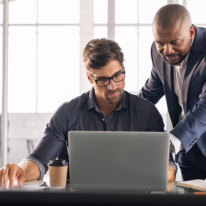 Business multiethnic colleagues having meeting in modern office. Smart business partners planning work together. Young businessman with boss working together on laptop.
